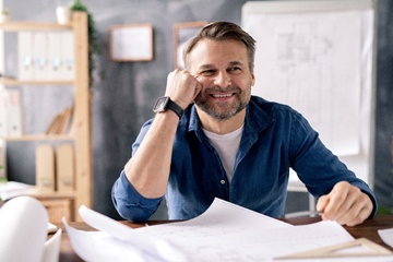 person smiling and looking over building blueprints