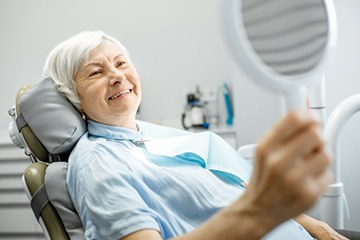Senior woman looking at smile in mirror