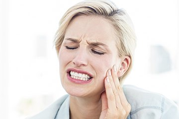 Woman holding cheek in pain