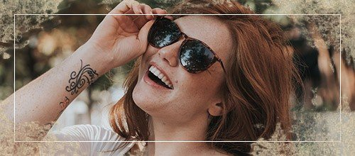 Woman with beautiful smile putting on sunglasses