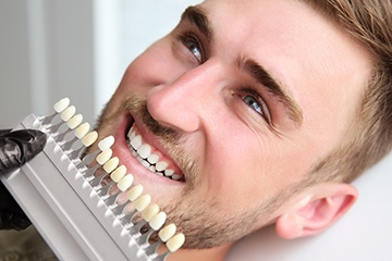 Man's smile compared with tooth shade chart