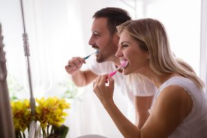 Man and woman brushing teeth