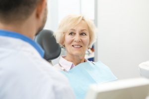 Older woman smiling in the dental chair after her dental implant surgery