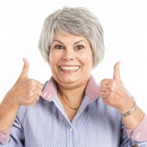 woman happy with dental implant cost in Naples