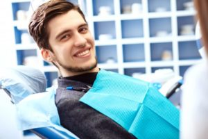 young man in dentist chair smiling